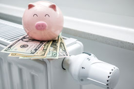foto of water-saving  - Heating thermostat with piggy bank and money expensive heating costs concept