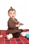Baby Girl Sitting On Blanket.
