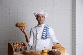 Baker in kitchen at table with freshly loaves of bread on white brick wall background