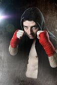 Man In Boxing Hoodie Jumper With Hood On Head With Wrapped Hands Wrists Ready To Fight