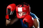 picture of headgear  - amateur boxer man training shadow boxing with red fighting gloves and headgear protection in defense stance isolated on black background - JPG