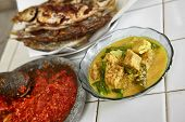 Indonesian local meal consisting sayur lodeh / vegetables with coconut milk soup and fried fish plus sambal / chili paste from Indonesia