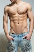 stock photo of hunk  - muscular sexy man in torn jeans stands near the sofa - JPG