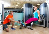 Calf extension woman at gym exercise machine workout and personal trainer woman