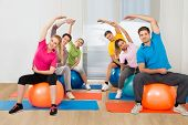 stock photo of pilates  - Group Of People Sitting On Pilates Ball Stretching - JPG