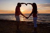 Couple Making Heart Shape At Beach