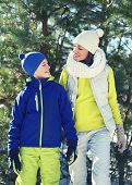 Family Walking In Winter Day, Happy Young Mother And Child Dressed In Bright Sportswear Have Fun Tog
