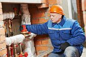 repairman engineer of engineering system or heating system installer open the valve equipment in a boiler house