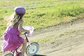 Little girl riding a bike on the country road.