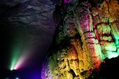 Colorfully lit stone formations in cave at guilin