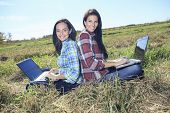 Young beautiful girls with laptop in a field