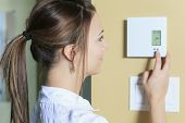 stock photo of carbon-footprint  - A woman set the thermostat at house - JPG