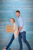 Young couple having fun on moving trolley against wooden planks