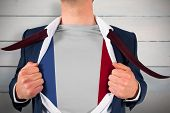 Businessman opening shirt to reveal france flag against painted blue wooden planks