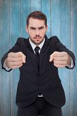 Angry businessman standing with clenched fists against wooden planks