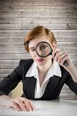 Redhead businesswoman looking through magnifying glass against wooden planks background
