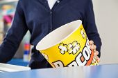Midsection of female worker holding empty popcorn tub at cinema concession stand