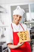 Portrait of beautiful female chef holding tray with stuffed ravioli pasta sheet in commercial kitchen