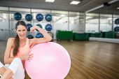 pic of fitness  - Cheerful fit woman flexing muscles by fitness ball against large empty fitness studio with shelf of exercise balls - JPG