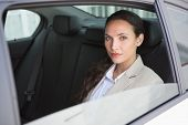 Unsmiling businesswoman looking at camera in her car