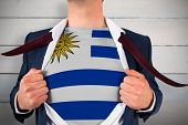 Businessman opening shirt to reveal uruguay flag against painted blue wooden planks