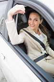Businesswoman smiling and holding key in her car