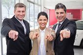 Smiling business team pointing at camera at new car showroom