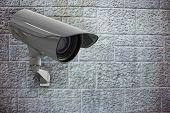 CCTV camera against grey brick wall