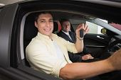 Happy male driver at the wheel sitting in his car at new car showroom