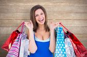 Cheerful brunette woman holding shopping bags against wooden surface with planks