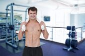 Fit shirtless man smiling at camera against empty weights room with bench press