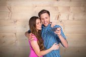 Cheerful young couple taking selfie with smart phone against bleached wooden planks background