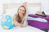 Smiling blond pointing a country on the globe in hotel country