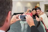 Businessman taking picture of the couple in their new car at new car showroom