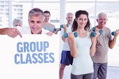 Casual man showing a poster against group classes