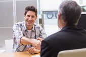 stock photo of showrooms  - Smiling customer shaking a salesman hand at new car showroom - JPG