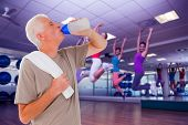 stock photo of zumba  - Composite image of senior man drinking from water bottle - JPG