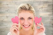 Attractive young blonde holding little hearts against bleached wooden planks background
