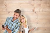 Attractive couple using their smartphones against bleached wooden planks background