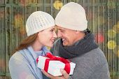 Casual couple in warm clothing holding gift against close up of christmas lights