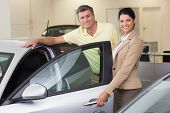 Businesswoman showing a car interior to her customers at new car showroom