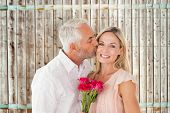 Affectionate man kissing his wife on the cheek with roses against wooden background in pale wood