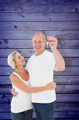 Mature couple smiling at camera with new house key against wooden planks background