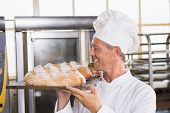 Baker holding tray of bread in the kitchen of the bakery