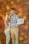 Attractive couple standing and using laptop against close up of christmas lights