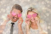 Attractive young couple holding pink hearts over eyes against light glowing dots design pattern