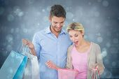 Attractive young couple holding shopping bags against blue abstract light spot design