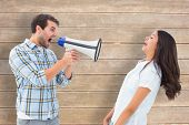 Angry man shouting at girlfriend through megaphone against wooden surface with planks