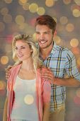 Attractive young couple smiling together against close up of christmas lights