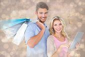 Attractive young couple holding shopping bags using tablet pc against light glowing dots design pattern